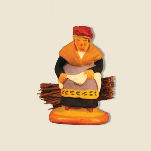 image: Old woman seated on a bundle of firewood